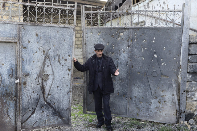 Elmar Abdullayev, 55, stands at a gates of his home hit by shelling in a village of Gapinli, in Terter region of Azerbaijan on Tuesday, April 5, 2016. Azerbaijan and separatist forces in Nagorno-Karabakhk on Tuesday agreed on a cease-fire starting noon local time following three days of the heaviest fighting in the disputed region since 1994, the Azeri defense ministry announced. Gapanli, a village south of Terter, has been one of the hardest hit. Houses bear the marks of the recent shelling; metal doors are riddled with shrapnel, power lines are cut down, craters are seen in the yards. (Photo by Hicran Babayev/AP Photo)