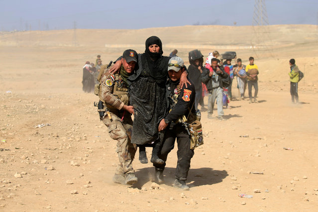Iraqi security forces help a displaced Iraqi woman flee her home as Iraqi forces battle with Islamic State militants in western Mosul, Iraq February 26, 2017. (Photo by Alaa Al-Marjani/Reuters)