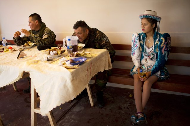 A performer rests as soldiers eat lunch in Surcubamba, Peru, Thursday, May 21, 2015. (Photo by Rodrigo Abd/AP Photo)