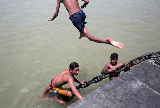 Indian boys jump into Ganges river to cool off during hot weather in Kolkata, India, 11 June 2019. India's Meteorological Department has issued a heatwave alert for five districts in Kolkata after hot weather saw the temperature reach over 36 degrees Celsius. (Photo by Piyal Adhikary/EPA/EFE)