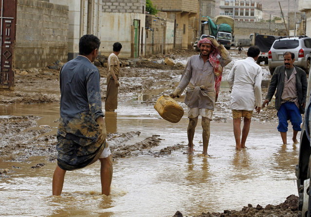 Yemenis walk through a flooded neighborhood following heavy rains in the northern city of Amran, Yemen, 14 April 2016. According to reports, at least 16 people have been died in a flash flood triggered by heavy rains in several Yemeni provinces on the same day. (Photo by Yahya Arhab/EPA)