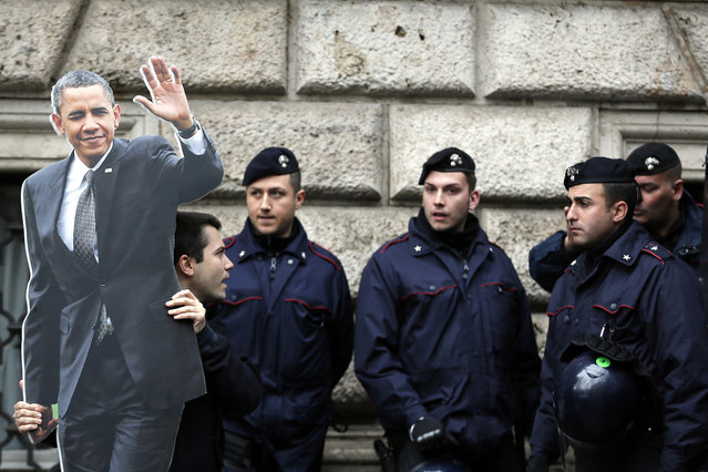"""A demonstrator holds a picture in front of Carabinieri's police during a protest against U.S. President Barack Obama near the U.S. Embassy in Rome, March 27, 2014. Obama urged NATO allies on Thursday to get their defense budgets on an upward trajectory with """"everybody pitching in"""" as he wounded up a day of meetings with Vatican and Italian officials. (Photo by Yara Nardi/Reuters)"""