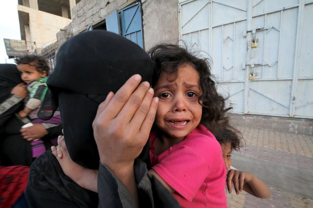 A girl cries next to her mother covering her face as they flee from an airstrike on an army weapons depot in Yemen's capital Sanaa May 11, 2015. (Photo by Mohamed al-Sayaghi/Reuters)