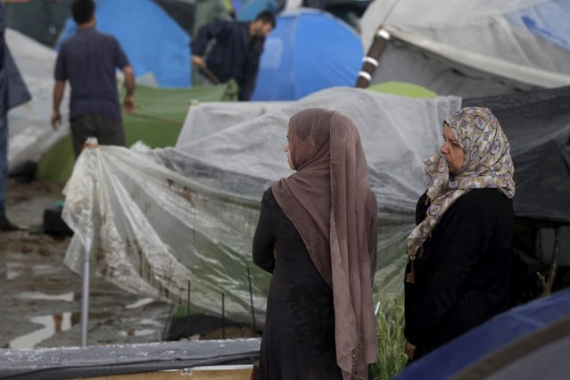 Two women stand next to tents at a makeshift camp for migrants and refugees at the Greek-Macedonian border near the village of Idomeni, Greece, April 24, 2016. (Photo by Alexandros Avramidis/Reuters)