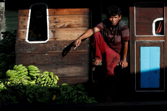 A man sits on the deck of a wooden ship in Tanjungpinang, on the island of Bintan, Indonesia, June 15, 2019. (Photo by Willy Kurniawan/Reuters)
