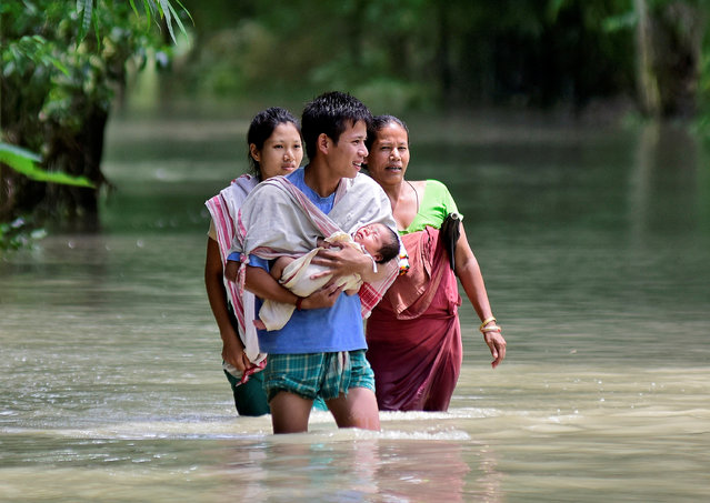 A man carries his new born baby as he and his family members wade through a flooded area to reach a relief camp at a village in Barpeta district of the northeastern state of Assam, India, July 25, 2019. (Photo by Anuwar Hazarika/Reuters)