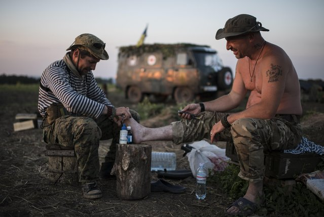 In this photo taken Monday, June 22, 2015, a Ukrainian serviceman from the Kiev-2 volunteer battalion renders assistance to his comrade at the frontline in the village of Krymske, east Ukraine. (Photo by Evgeniy Maloletka/AP Photo)