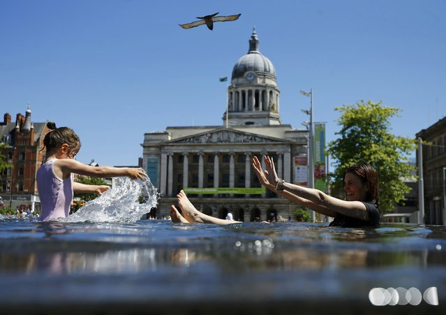 Tatiana and Anneke Toth aged four, play in a fountain in Nottingham, Britain June 30, 2015. (Photo by Darren Staples/Reuters)