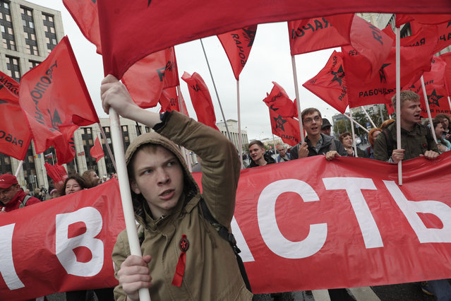 Communist party supporters wave red flags during a protest in the center of Moscow, Russia, Saturday, August 17, 2019. People rallied Saturday against the exclusion of some city council candidates from Moscow's upcoming election. (Photo by AP Photo/Stringer)