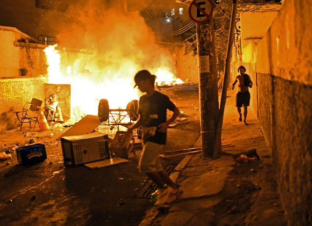 Residents run for cover during violent clashes between protestors and Brazilian Police Special Forces in a favela near Copacabana in Rio de Janeiro, Brazil on April 22, 2014. Violent protests broke out in Rio's landmark beachfront district, Copacabana, following the death of a resident last weekend during clashes with the Army in a nearby favela. (Photo by Christophe Simon/AFP Photo)