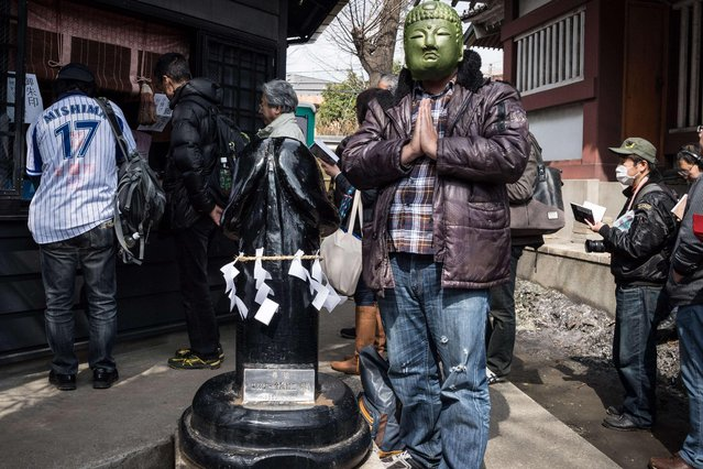 A participant prays near a giant phallus during the Kanamara Matsuri Steel Phallus Festival at Kawasaki, Japan on April 2, 2017. (Photo by DELETREE/SIPA Press/Rex Features/Shutterstock)