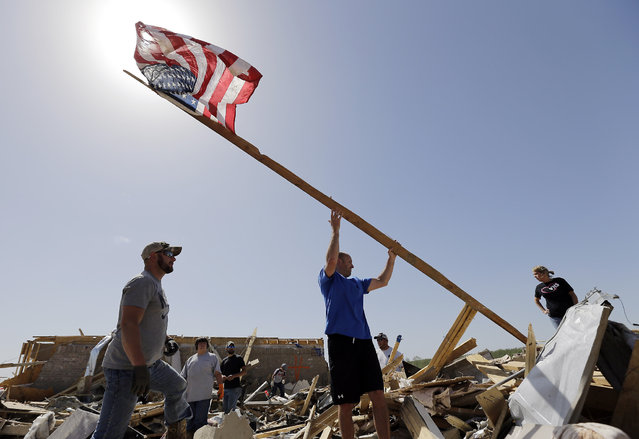 Justin Shaw, left, helps Nick Conway erect a flag pole at his home that was destroyed by a tornado, Monday, April 28, 2014, in Vilonia, Ark. (Photo by Eric Gay/AP Photo)