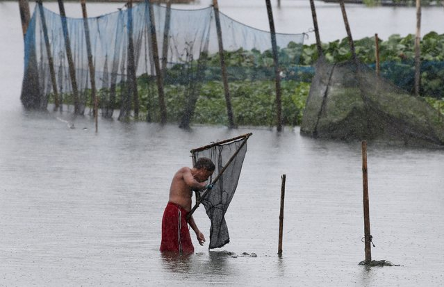 A fisherman checks his net for fresh catch amidst bad weather at Laguna de Bay, in Paranaque, Metro Manila July 6, 2015. All shipping was ordered to remain in harbour and some flights were cancelled in the northern Philippines, while schools were closed in the capital, Manila, on Monday due to flooding and landslides from a tropical storm, disaster officials said. (Photo by Erik De Castro/Reuters)