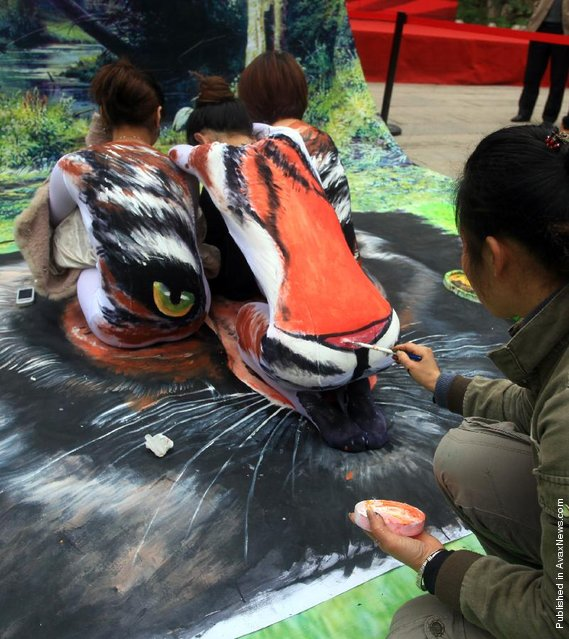 A street painter paints a tiger on the backs of three models at the Three Lanes and Seven Alleys in Fuzhou, China