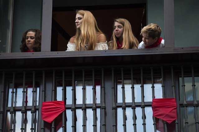 People watch from a balcony decorated with a red kerchief at the beginning of the third running of the bulls, at the San Fermin Festival, in Pamplona, Spain, Thursday, July 9, 2015. (Photo by Alvaro Barrientos/AP Photo)