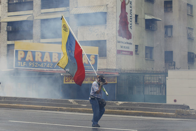 A demonstrator carries a Venezuelan flag amidst tear gas during anti-government protests in Caracas, Venezuela, Wednesday, April 19, 2017. (Photo by Ariana Cubillos/AP Photo)