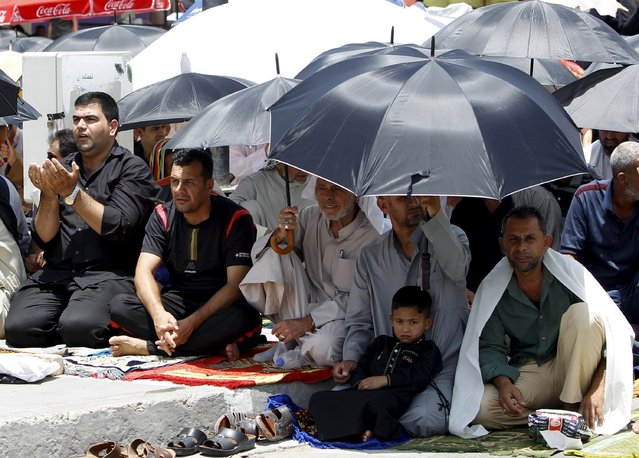 Shi'ite Muslims hold umbrellas to shelter themselves from the sun as they attend Friday prayers in Baghdad's Sadr City July 10, 2015. (Photo by Ahmed Saad/Reuters)