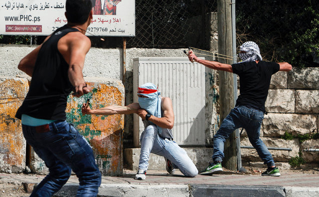 Palestinian protesters use slingshots to hurl stones towards Israeli security forces during clashes following a demonstration in the West Bank town of Bethlehem on April 21, 2017, in solidarity with Palestinians imprisoned in Israeli jails after hundreds of detainees launched a hunger strike earlier on April 17. Some 1,500 Palestinian prisoners have joined the hunger strike that began earlier this week, following a call from Palestinian leader and prominent prisoner Marwan Barghouti, a Palestinian Authority official said. (Photo by Musa Al Shaer/AFP Photo)