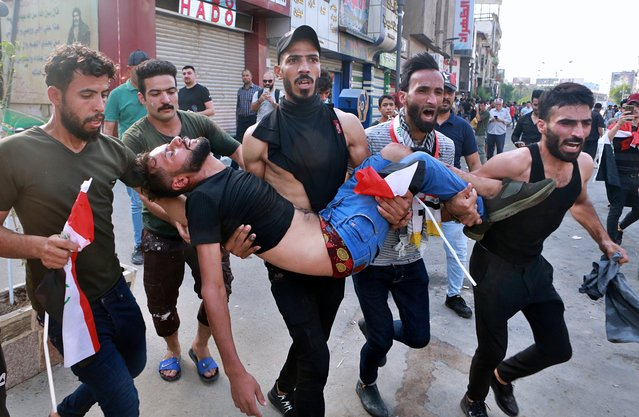 An injured protester is carried after reacting to tear gas fired by security forces during a protest in Tahrir Square, in central Baghdad, Iraq, Tuesday, October 1, 2019. (Photo by Khalid Mohammed/AP Photo)