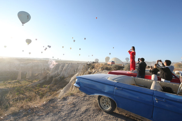 Tourists take photos as hot air balloons glide over Goreme district during early morning at the historical Cappadocia region, located in Central Anatolia's Nevsehir province, Turkey on September 30, 2019. Cappadocia is preserved as a UNESCO World Heritage site and is famous for its chimney rocks, hot air balloon trips, underground cities and boutique hotels carved into rocks. In Turkey's one of the most important tourism regions Cappadocia, local and foreign tourists get the chance of enjoying the scenery participating air balloon tours in the early hours of the morning. (Photo by Sercan Kucuksahin/Anadolu Agency via Getty Images)