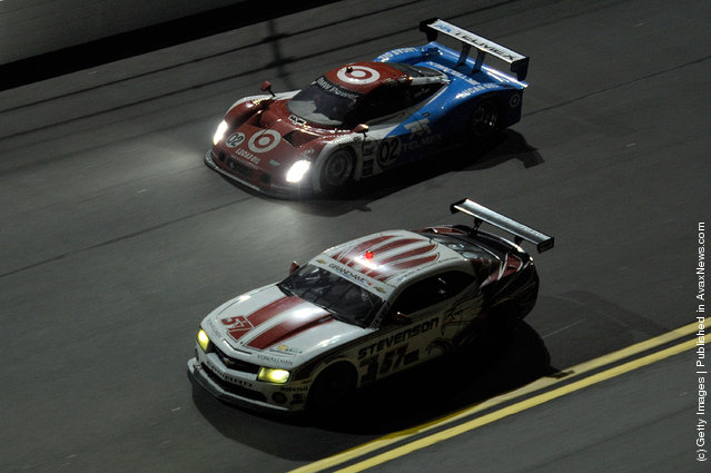 The #57GT Camero GTR driven by Robin Liddell, John Edwards, and Ronnie Bremer race with the #02 DP Target/TELMEX driven by Scott Dixon, Dario Franchitti, Juan Pablo Montoya and Jamie McMurray during the Rolex 24 at Daytona International Speedway