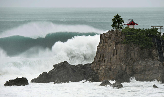 In this July 16, 2015 photo, waves crash against Katsurahama in Kochi on the island of Shikoku, western Japan, as a strong tropical storm sweeps across western Japan. Tropical Storm Nangka caused serious flooding Friday morning, July 17,  and disrupted air and train travel as it crossed the island of Shikoku and the main Japanese island of Honshu. (Photo by Kyodo News via AP Photo)