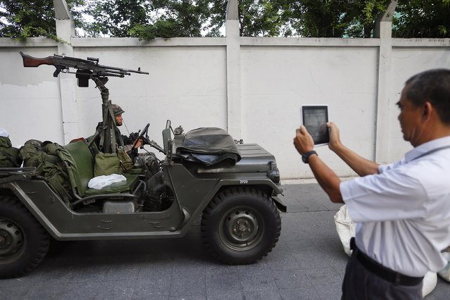 A man takes pictures of a soldier sitting in a military vehicle, with a machine gun mounted on it, after the Thai army took their positions in central Bangkok May 20, 2014. Thailand's army declared martial law on Tuesday to restore order after six months of anti-government protests which have left the country without a proper functioning government, but the move did not constitute a coup, military officials said. (Photo by Damir Sagolj/Reuters)