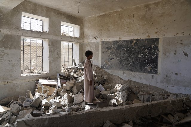 A student at the Aal Okab school stands in the ruins of one of his former classrooms, which was destroyed during the conflict in June 2015. Students now attend lesson in UNICEF tents nearby. (Photo by Giles Clarke for UN-OCHA/Getty Images)