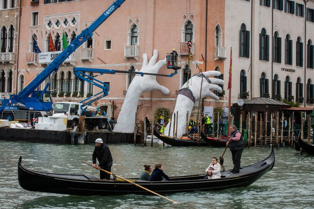 "Workers finish to prepare the exhibition ""SUPPORT"" by Lorenzo Quinn, during the 57th Biennale Arte on May 11, 2017 in Venice, Italy. The 57th International Art Exhibition of La Biennale di Venezia will be open to the public from the June 13 to November 26, 2017. (Photo by David Levene/The Guardian)"