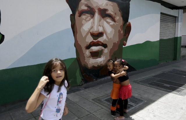 Girls embrace in front of a mural depicting late Venezuelan President Hugo Chavez, at a street in Caracas July 10, 2015. (Photo by Jorge Dan Lopez/Reuters)
