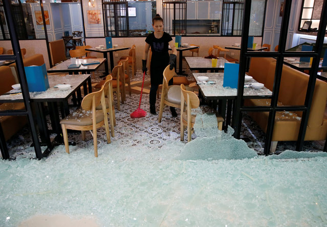 An employee clears shattered glass after anti-government protesters vandalised a restaurant during a demonstration at New Town Plaza shopping mall in Hong Kong, China, October 13, 2019. (Photo by Umit Bektas/Reuters)