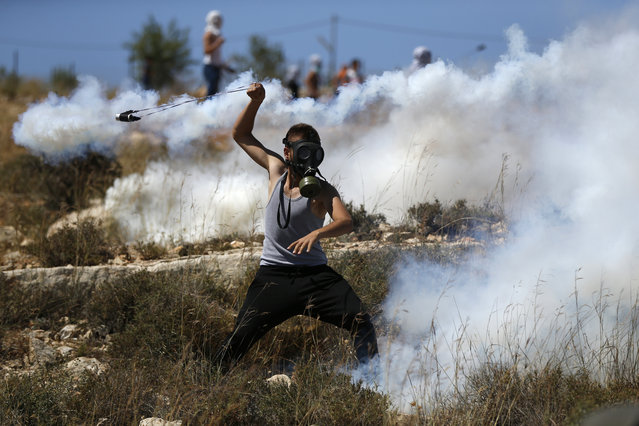 A Palestinian protester hurls back a tear gas canister fired by Israeli troops during a demonstration by in the village of Nabi Saleh, north of Ramallah, in the Israeli-occupied West Bank on May 26, 2017. (Photo by Abbas Momani/AFP Photo)