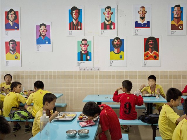 Young Chinese football players eat lunch under caricatures of famous footballers in the canteen at the Evergrande International Football School near Qingyuan in Guangdong Province. (Photo by Kevin Frayer/Getty Images)