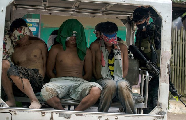 Blindfolded suspected self-styled Islamic State (IS) group members are transported in a police vehicle after being captured in a village in Marawi City on the southern island of Mindanao on June 3, 2017. Hundreds of Islamist gunmen rampaged through the city of 200,000, the Islamic capital of the mainly Catholic Philippines, on May 23 after government forces attempted to arrest their leader, Isnilon Hapilon. Up to 50 gunmen continued to control downtown Marawi nearly two weeks later with at least 15 hostages including a Catholic priest, with some being used as human shields, the military said. (Photo by Noel Celis/AFP Photo)