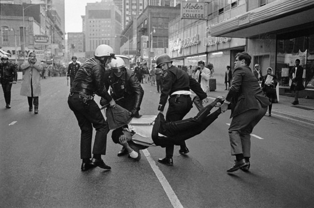"Police haul a youth to the paddy wagon as an undetermined number of arrest were made in downtown Atlanta, Georgia, February 25, 1971, as police moved in to disperse black youths after windows were broken and rocks and fruit thrown in what officers called ""a major disturbance"". (Photo by Charles Kelly/AP Photo)"
