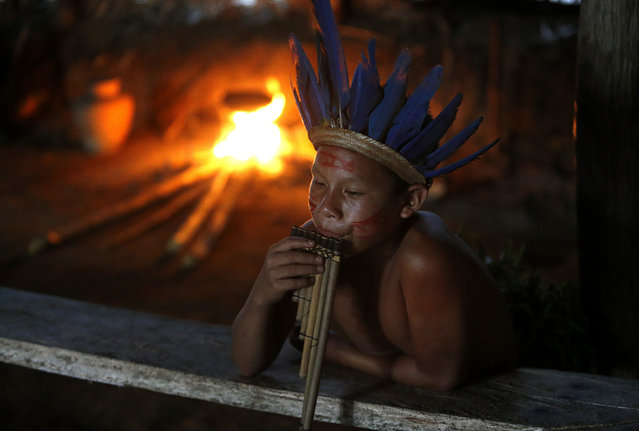 A member of the AmazonianTatuyo tribe plays music in his village in the Rio Negro (Black River) near Manaus city, a World Cup host city, June 23, 2014. Because of their proximity to host city Manaus and their warm welcome, the Tatuyo have enjoyed three weeks of brisk business thanks to the World Cup. Usually, they host between 10 and 30 tourists a day. During the World Cup, this number has rocketed to 250 a day, They have become richer and other communities now come to them to sell them juices and fishes. (Photo by Andres Stapff/Reuters)