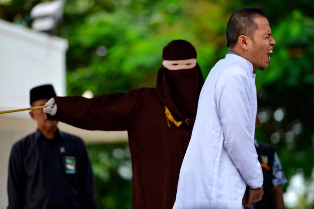 Aceh Ulema Council (MPU) member Mukhlis reacts as he is whipped in public by a member of the Sharia police in Banda Aceh on October 31, 2019. An Indonesian man working for an organisation which helped draft strict religious laws ordering adulterers to be flogged was himself publically whipped on October 31 after he was caught having an affair with a married woman. (Photo by Chaideer Mahyuddin/AFP Photo)