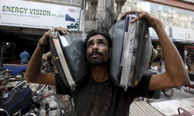 A man carries secondhand monitor picture tubes to install in homemade television sets at a market in Karachi, Pakistan, July 29, 2015. A handmade television set is a blend of secondhand monitor picture tube and assembled circuit cards, which are available in the market at prices of around Pakistani Rupees 3500 to 4200 ($34 and 41) each depending on size. (Photo by Akhtar Soomro/Reuters)