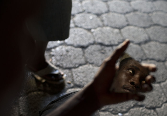 In this June 27, 2015 photo, a man uses a shard of mirror to check his reflection as he passes the time with other residents inside the abandoned shipping depot where they live in Port-au-Prince, Haiti. Some residents of the building have full-time jobs, while others are partially-employed or look for day work. (Photo by Rebecca Blackwell/AP Photo)