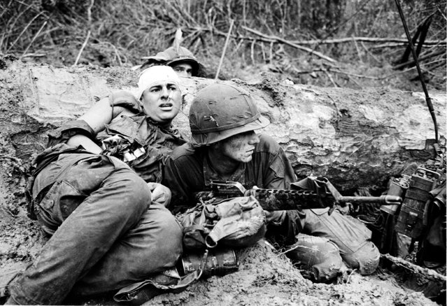 An American soldier, right, is positioned over his rifle as he protects his wounded buddy crouched in front of a log in the thick mud during battle against North Vietnamese in War Zone D near Phuoc Vinh, Vietnam, June 15, 1967. The B Company of the 1st Battalion, 16th Infantry, 1st Division fought a 30-minute battle and lost 6 men with 12 wounded.  Another marine can be seen behind the log. (Photo by Henri Huet/AP Photo)