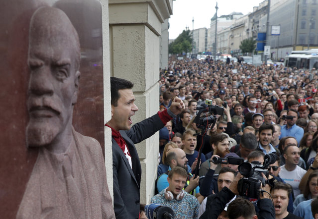 Russian opposition candidate Russian and activist Ilya Yashin, center, gestures while speaking to a crowd next to a bas-relief of the Soviet founder Vladimir Lenin, left, during a protest in Moscow, Russia, Sunday, July 14, 2019. Opposition candidates who run for seats in the city legislature in September's elections have complained that authorities try to bar them from the race by questioning the validity of signatures of city residents they must collect in order to qualify for the race. (Photo by Pavel Golovkin/AP Photo)