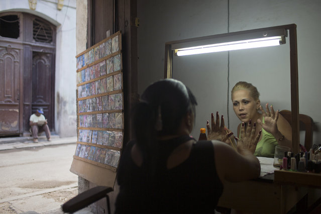 Manicurist Raquelin Reyes (R), 30, works at her home in downtown Havana December 19, 2014. (Photo by Alexandre Meneghini/Reuters)