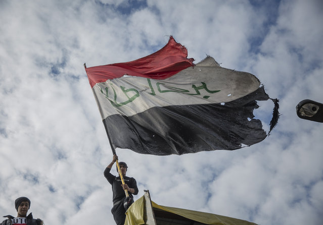 An anti government protester flies an Iraqi flag on top of cement blocks that separate protesters from riot police, during the ongoing protests in Tahrir square, Baghdad, Iraq, Friday, January 10, 2020. (Photo by Nasser Nasser/AP Photo)