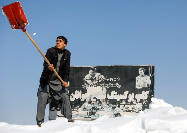 An Afghan man removes snow in font of a poster depicting boxing legend Muhammad Ali, as snow covers the streets Kabul, Afghanistan on January 7, 2020. (Photo by Mohammad Ismail/Reuters)