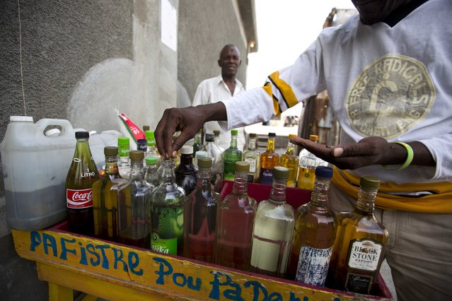 Eddy Lecty, who sells a sugar-based alcoholic drink known as clairin, adds cloves to spice up one of his bottles in the Cite Soleil area of Port-au-Prince, Haiti, Tuesday, July 11, 2017. Individual retailers who add flavors with herbs or fruit to the less refined version of rum reuse bottles carrying other labels. (Photo by Dieu Nalio Chery/AP Photo)