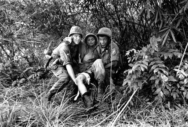 Trying to avoid intense sniper fire, two American medics carry a wounded paratrooper to an evacuation helicopter during the Vietnam War on June 24, 1965