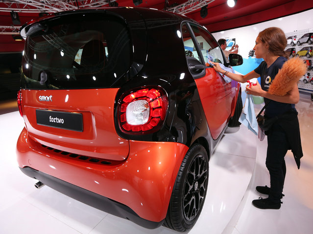 An employee cleans a Smart ForTwo car on display at the presentation of the latest models of Daimler's two-seater ForTwo and four-seater ForFour Smart cars on July 16, 2014 in Berlin, Germany. Smart, whose sales fell 10 percent to 46,816 in first half of the year, says that the ForFour will be aimed at young people who would prefer more space than that of the ForTwo. Both cars will be built at the Renault factory in Slovenia. (Photo by Adam Berry/Getty Images)