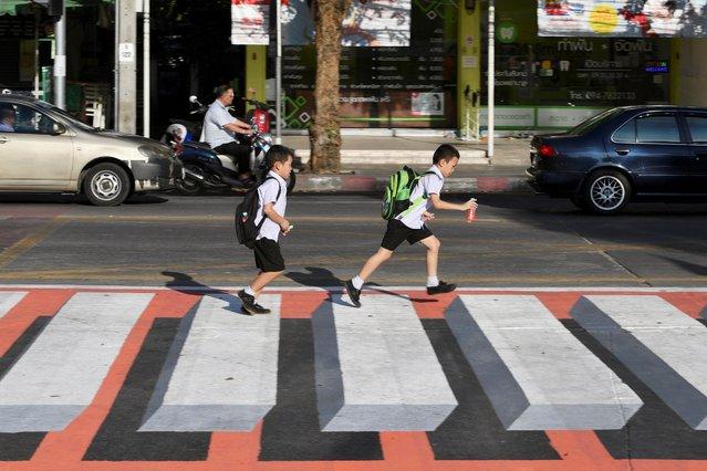 Children walk past a 3D pedestrian crossing in Bangkok, Thailand on November 28, 2019. (Photo by Chalinee Thirasupa/Reuters)