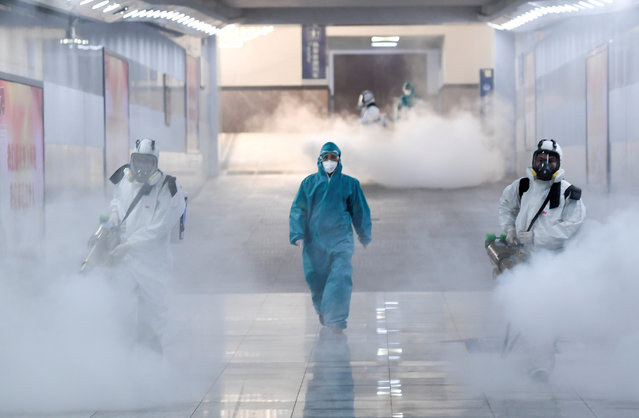 Volunteers in protective suits disinfect a railway station as the country is hit by an outbreak of the new coronavirus, in Changsha, Hunan province, China on February 4, 2020. (Photo by Cnsphoto via Reuters)