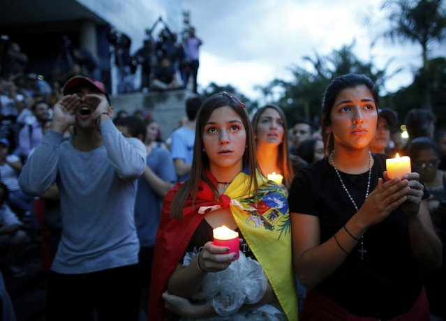 Anti-government demonstrators hold candles during a vigil in honor of those who have been killed during clashes between security forces and demonstrators in Caracas, Venezuela, Monday, July 31, 2017. Many analysts believe Sunday's vote for a newly elected assembly that will rewrite Venezuela's constitution will catalyze yet more disturbances in a country that has seen four months of street protests in which at least 125 people have died. (Photo by Ariana Cubillos/AP Photo)